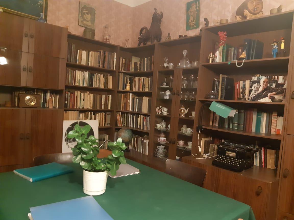зеленая скатерть на столе Льва Гумилева и книжные полки забитые книги.